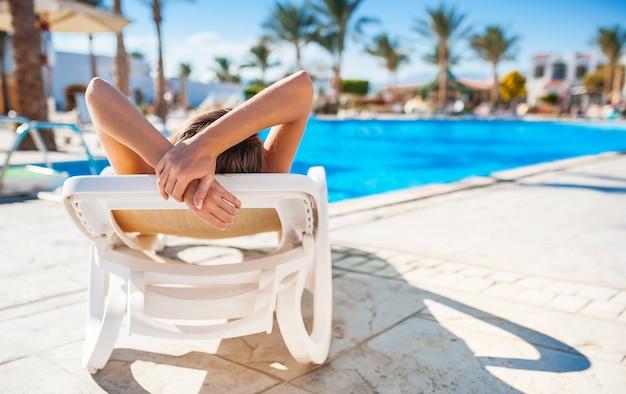 Piękna młoda kobieta relaksuje na słońca lounger pobliskim basenie.