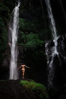 Piękna młoda kobieta relaksuje przed siklawą w bikini. ekoturystyka koncepcja obrazu dziewczyna podróży