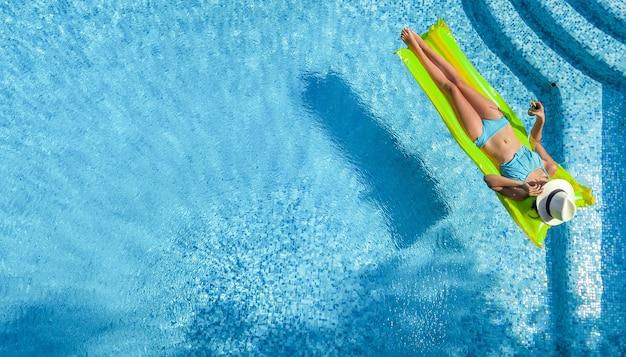 Piękna młoda kobieta relaksuje się w basenie dziewczyna pływa na nadmuchiwanym materacu i dobrze się bawi