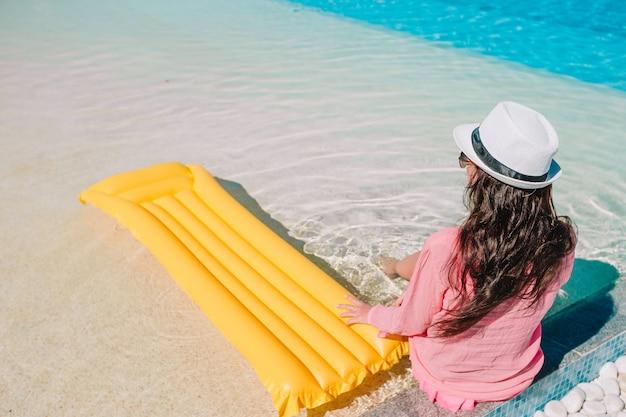 Piękna młoda kobieta relaksuje w pływackim basenie, szczęśliwa dziewczyna w plenerowym basenie przy luksusowym hotelem