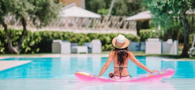 Piękna młoda kobieta relaksuje w pływackim basenie.