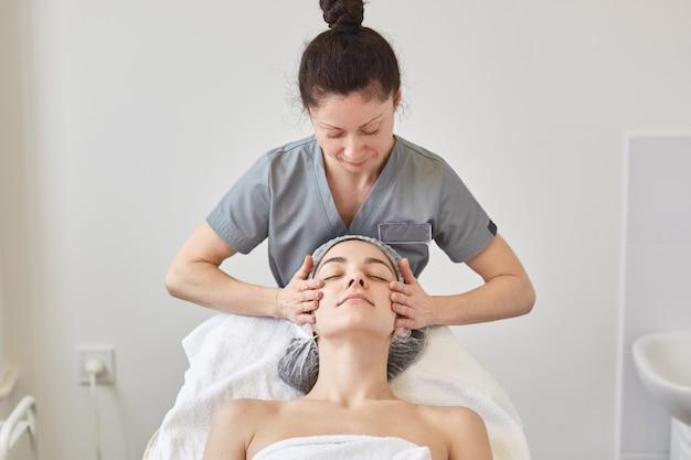 Piękna młoda kobieta relaksuje z twarz masażem przy piękno zdrojem podczas gdy kłamający