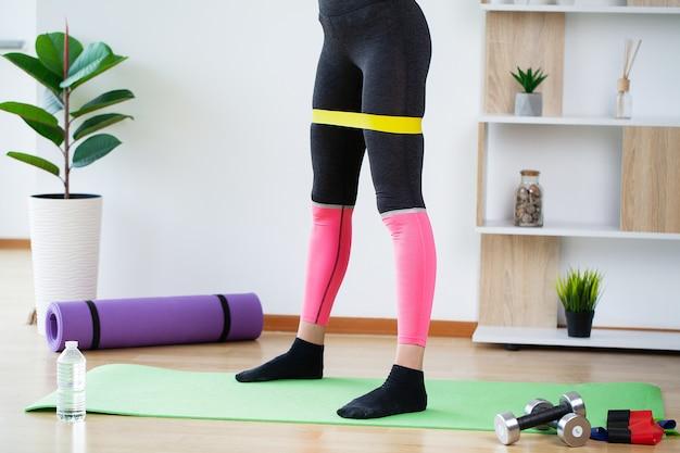 Piękna młoda kobieta robi ćwiczenia fitness w domu.