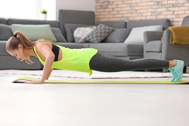 Piękna młoda kobieta robi ćwiczenia fitness w domu