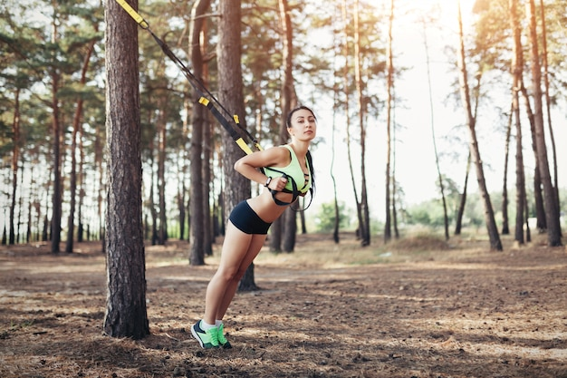 Piękna młoda kobieta robi ćwiczenia trx z zawiesia trenera procy w plenerze zdrowy