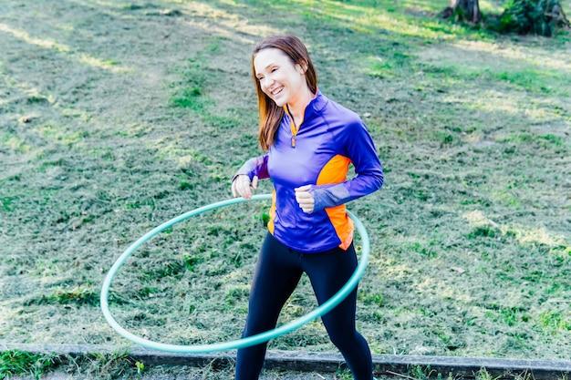 Piękna młoda kobieta robi hula hop o zachodzie słońca w parku punkt koncepcja sport gimnastyka higieniczna higiena osobista