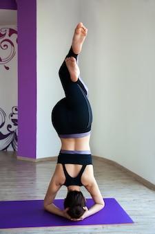 Piękna młoda kobieta robi joga asana blisko okno