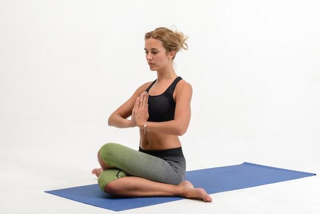 Piękna młoda kobieta robi joga na biel ścianie