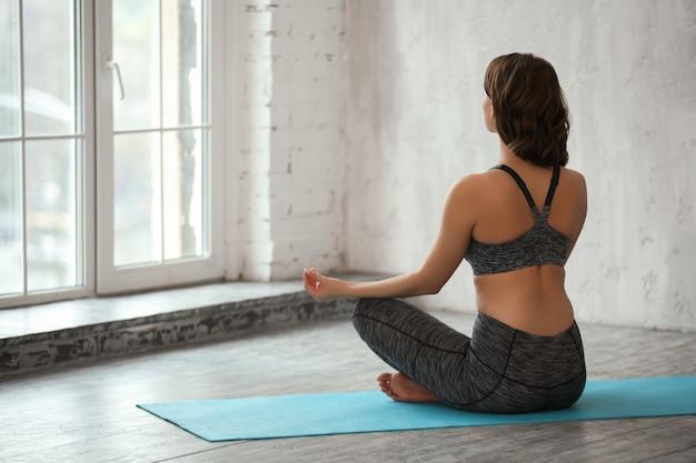 Piękna młoda kobieta robi joga w domu