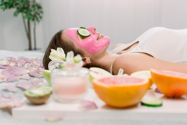 Piękna młoda kobieta robi masaż twarzy glinką w spa, leżąc z ogórkami na oczach. widok z boku.