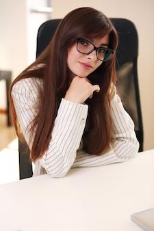 Piękna młoda kobieta robi papierkową robotę siedząc przy biurku w biurze
