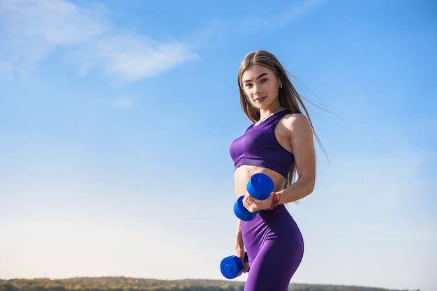 Piękna młoda kobieta robi poranne ćwiczenia z hantlami na świeżym powietrzu zdrowego stylu życia