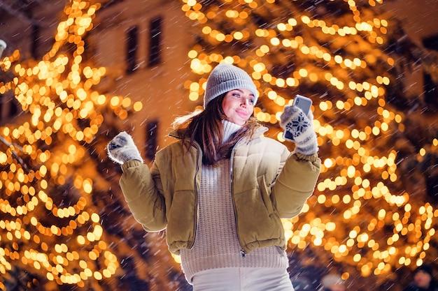 Piękna młoda kobieta robi selfie lub używa telefonu na zewnątrz