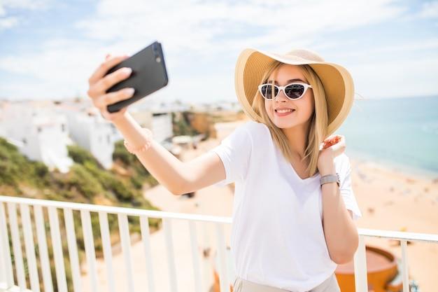 Piękna młoda kobieta robi selfie na telefon na plaży