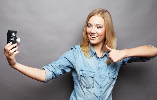 Piękna młoda kobieta robi selfie zdjęcie z aparatem.