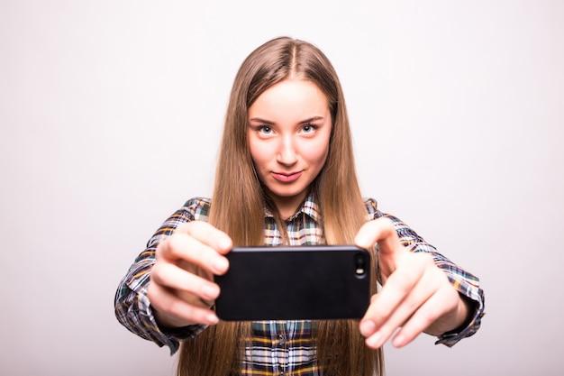 Piękna młoda kobieta robi selfie zdjęcie z smartphone na białym tle na białej ścianie
