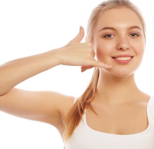Piękna młoda kobieta robi wezwaniu ja gest