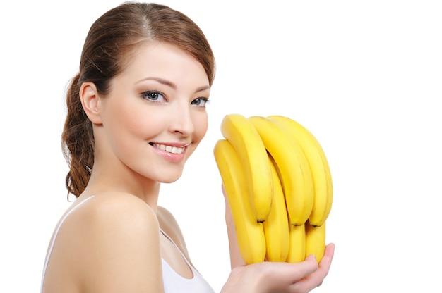 Piękna młoda kobieta roześmiany z bananami na białym tle