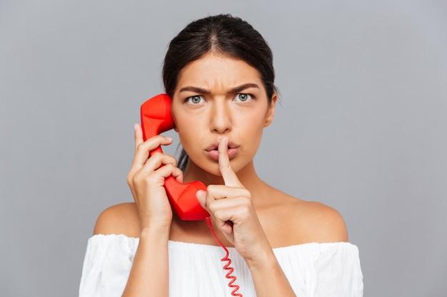 Piękna młoda kobieta rozmawia przez rurkę telefonu i pokazuje gest ciszy na szarej ścianie