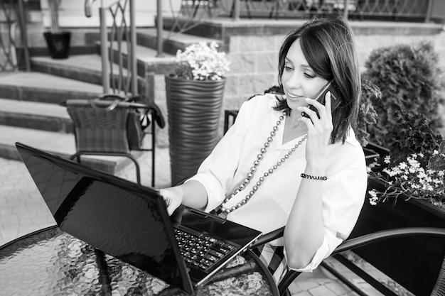 Piękna młoda kobieta rozmawia przez telefon komórkowy i pracy z laptopem, siedząc w kawiarni miejskiej na zewnątrz. obraz czarno-biały