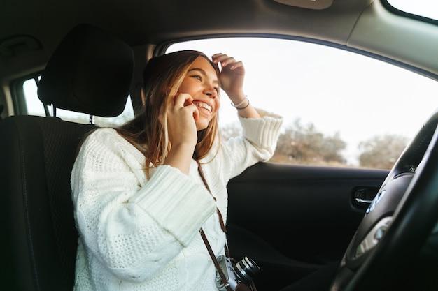 Piękna młoda kobieta rozmawia przez telefon komórkowy siedząc w samochodzie