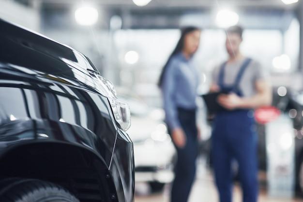 Piękna młoda kobieta rozmawia z przystojnym mechanikiem samochodowym podczas naprawy samochodu w salonie