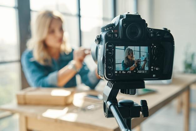 Piękna młoda kobieta rozpakowuje coś podczas pracy przed aparatem cyfrowym