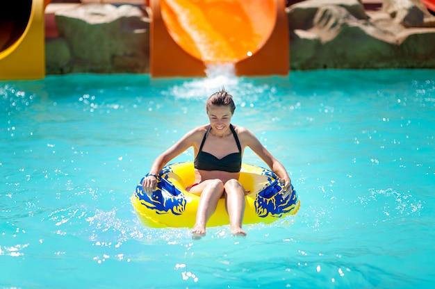 Piękna młoda kobieta ściąga zjeżdżalnie w parku wodnym