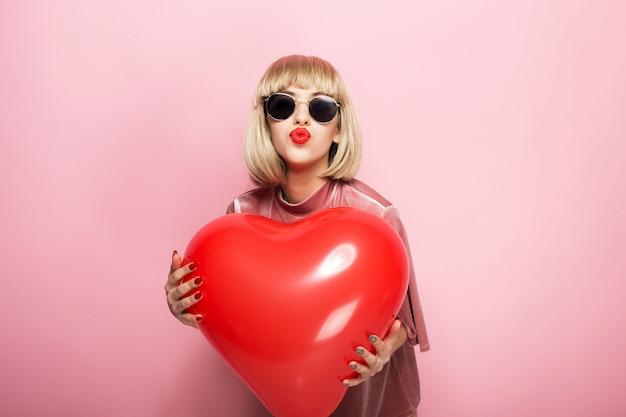 Piękna młoda kobieta ściska w kształcie serca czerwoną piłkę i buziaki. na różowym tle.