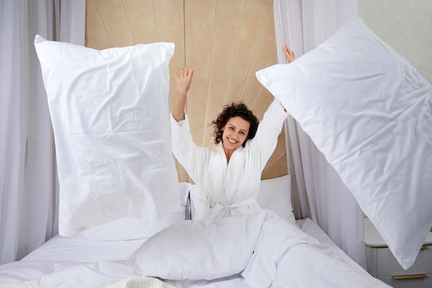 Piękna młoda kobieta siada na łóżku i rzuca poduszką w domu, bawiąc się bawiąc się w weekend