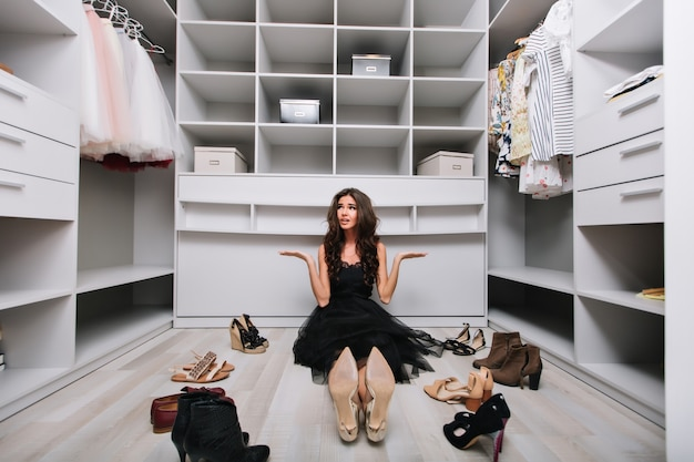 Piękna młoda kobieta siedząca na podłodze w dużej, ładnej garderobie wokół butów, nie wie w co się ubrać, rozczarowana i zmęczona dokonywaniem wyboru. ubrana w czarną sukienkę.