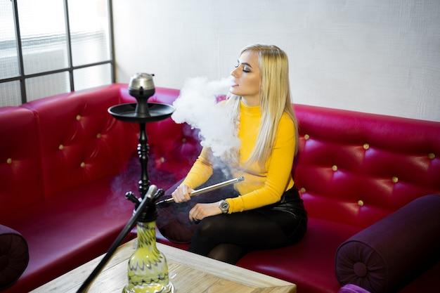 Piękna młoda kobieta siedzi na czerwonej skórzanej kanapie i pali fajkę wodną.