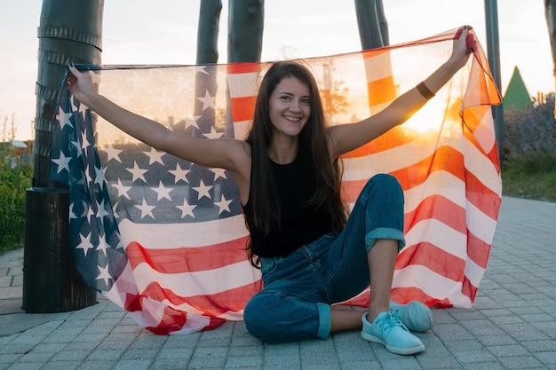 Piękna młoda kobieta siedzi na deskorolce i trzymając flagę usa w parku o zachodzie słońca