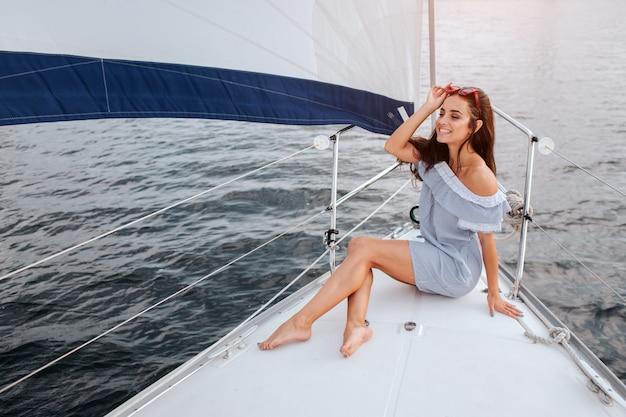 Piękna młoda kobieta siedzi na jachcie miskę i pozuje. trzyma czerwone okulary na głowie ręką i uśmiechem. model żegluje na pokładzie jachtu.