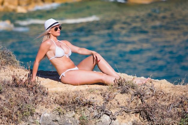 Piękna młoda kobieta siedzi na kamieniu nad brzegiem morza