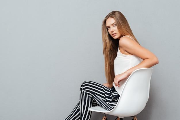 Piękna młoda kobieta siedzi na krześle na białym tle na szarym tle