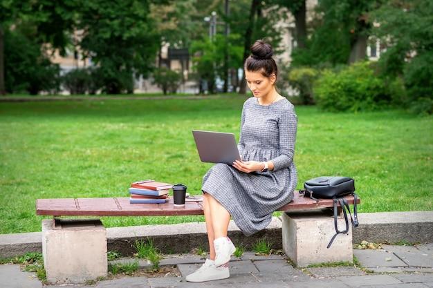 Piękna młoda kobieta siedzi na ławce z laptopem i pracuje lub studiuje na świeżym powietrzu