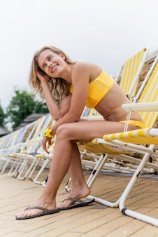 Piękna młoda kobieta siedzi na leżaku przy basenie