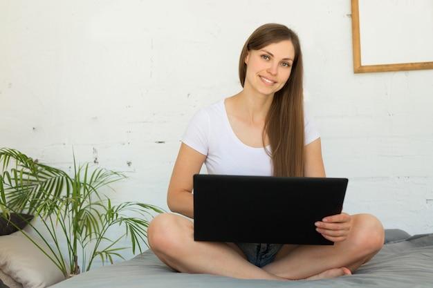 Piękna młoda kobieta siedzi na łóżku z laptopem w domu