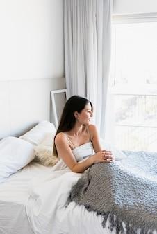 Piękna młoda kobieta siedzi na łóżku z szarym dywanie