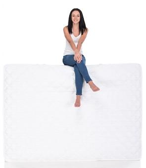 Piękna młoda kobieta siedzi na materacu.