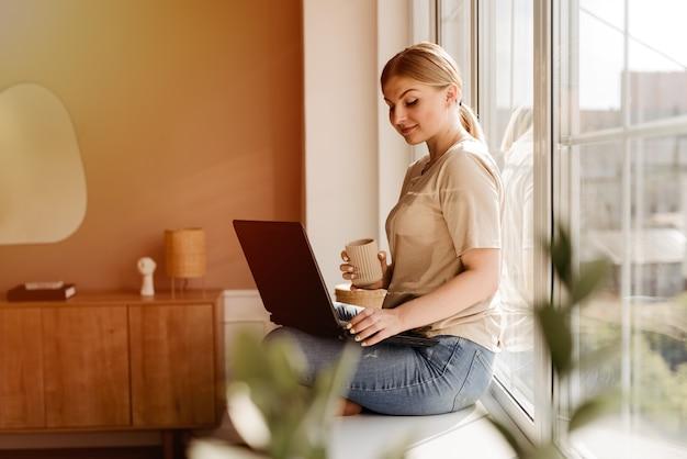 Piękna młoda kobieta siedzi na parapecie z laptopem i filiżanką kawy