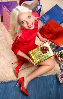 Piękna młoda kobieta siedzi na podłodze wśród toreb na zakupy i pudełek ze świątecznymi prezentami