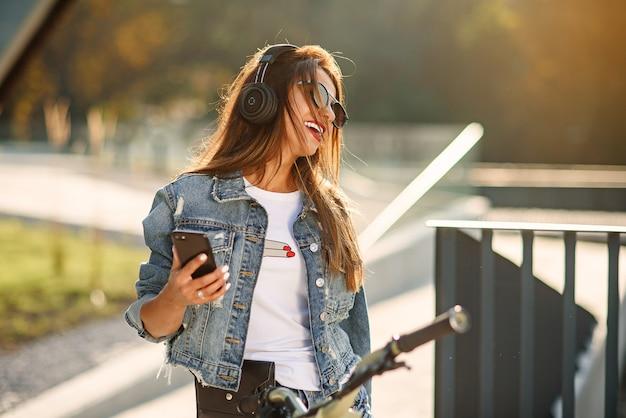 Piękna młoda kobieta siedzi na rowerze na zewnątrz w przestrzeni miejskiej, słucha muzyki za pomocą bezprzewodowych słuchawek z telefonem komórkowym. ciesz się pięknymi chwilami życia. aktywny styl życia.