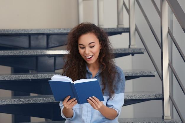 Piękna młoda kobieta siedzi na schodach i czyta książkę
