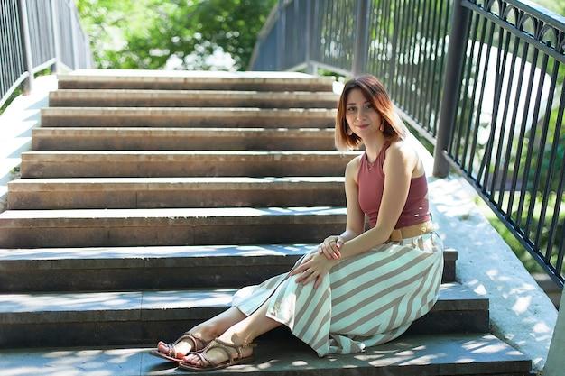 Piękna młoda kobieta siedzi na schodach mostu w letni dzień.