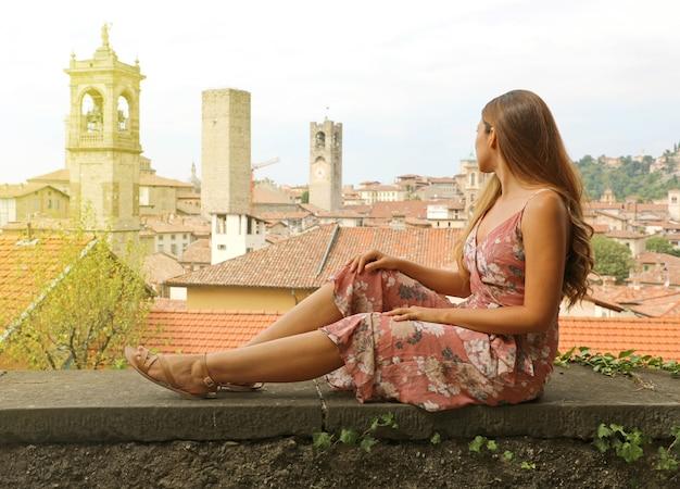 Piękna młoda kobieta siedzi na ścianie patrząc na włoskie średniowieczne stare miasto bergamo we włoszech.