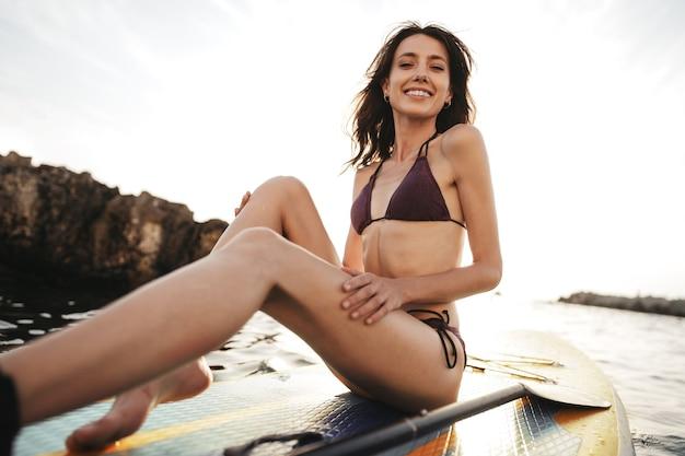 Piękna młoda kobieta siedzi na stojącej desce wiosłowej w morzu