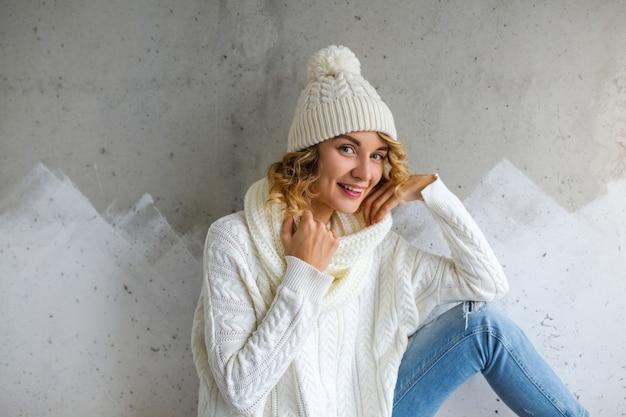 Piękna młoda kobieta siedzi przed ścianą na sobie biały sweter i dżinsy