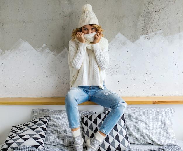 Piękna młoda kobieta siedzi przed ścianą na sobie biały sweter